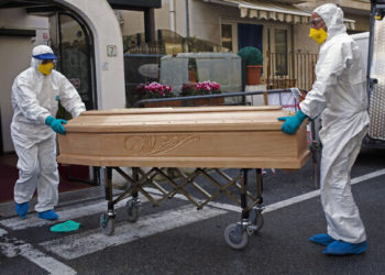 Medical staff wearing protective suits carry the coffin containing the body of Assunta Pastore, 87, after she passed away in her room at the Garden hotel in Laigueglia, northwest Italy, Liguria region, Sunday March 1, 2020. The woman, part of a group of elderly tourist from the Lombardia region, tested positive of the COVID-19. The hotel has been placed under quarantine as Italy continued to scramble Sunday to contain the spread of the corona virus. (AP Photo)