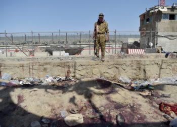 A Taliban fighter stands guard at the site of the August 26 twin suicide bombs, which killed scores of people including 13 US troops, at Kabul airport on August 27, 2021. (Photo by WAKIL KOHSAR / AFP)
